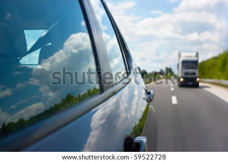 View through the rear mirror on the approaching truck on the highway. Beautiful reflections of the clouds in the windows. Shallow depth of field. - stock photo