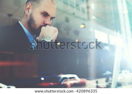 View through the window of a cafe with double exposition of young serious man successful trader is monitoring exchange trading via laptop computer, while is sitting in modern coffee shop interior - stock photo