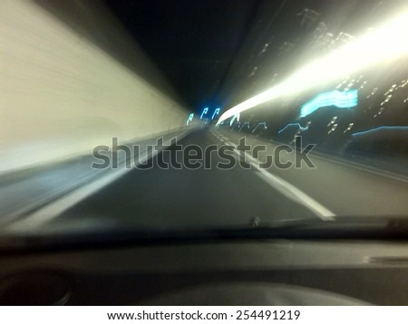 View through the windscreen of the road ahead with motion blur and lights as a vehicle speeds through an underground tunnel - stock photo