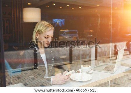 View through window of woman is chatting with friends in social network via cell phone, while is resting after on-line training via laptop computer. Hipster girl is typing text message on mobile phone - stock photo