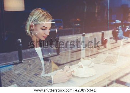 View through window of young female student is playing games on mobile phone, while is waiting for her college friends in cafe before lectures in university. Hipster girl is browsing feminine website - stock photo