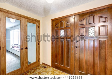 View to brown wooden enterance door. Tile floor and carpet floor in the next room. Glass transparent door - stock photo