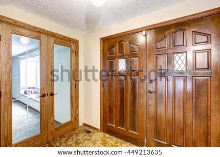 View to brown wooden enterance door. Tile floor and carpet floor in the next room. Glass transparent door - stock photo