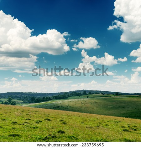 view to green hills and deep blue sky with low clouds over it - stock photo