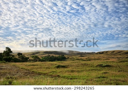 View to hills of savanna under stunning sunny cloudy sky  - stock photo