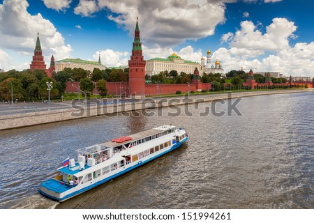 View to Moscow Kremlin from Bolshoi Kamenniy bridge over river with ship under clouds, Russia