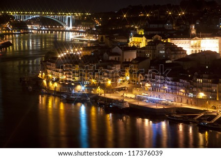 View to Porto over river Douro with reflection of the lights at night