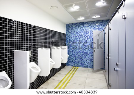 View to public toilet with grey cubicles and white urinals - stock photo