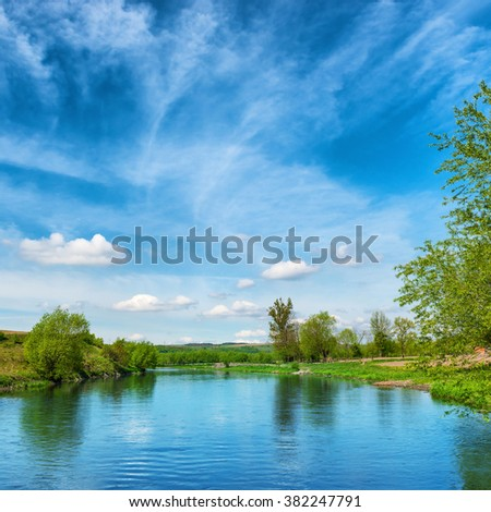 View to river banks with green trees and blue cloudy sky - stock photo