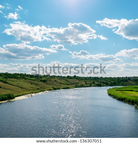 view to river with reflections under cloudy sky - stock photo