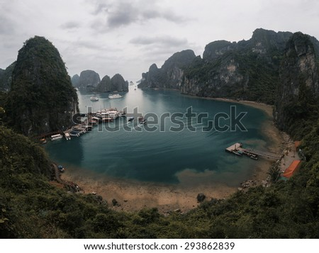 View to the calm lagoon with pier and boats situated in Ha Long Bay, Vietnam - stock photo