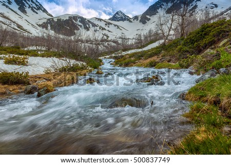 View to the foothills of the Caucasus mountains over stream near Arkhyz, Karachay-Cherkessia, Russia