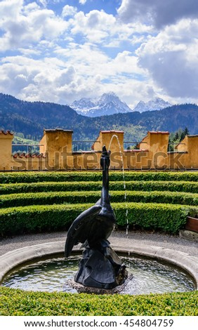 View to the fountain with black swan and green fence, on the background mountains peaks under clouds on the blue sky, Bavaria, Germany