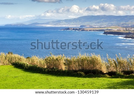 View to the green field, town and mountains at the Atlantic ocean coast, San Miguel, Azores, Portugal - stock photo