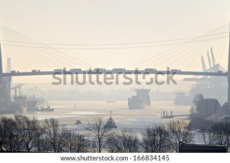"""View to the """"Koehlbrandbruecke"""" in Hamburg in Wintertime. The """"Koehlbrandbruecke"""" is an important suspension bridge in the harbor of Hamburg - stock photo"""