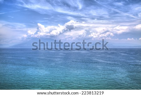View to the Lake Garda with dramatic effects in blue-green colors and a sculptural cloudy sky - stock photo