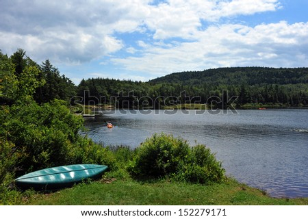 View to the mountain lake upstate ny at the summer time with kayak boat at the foreground - stock photo