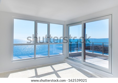 view to the sea from a windows in epmty white room - stock photo