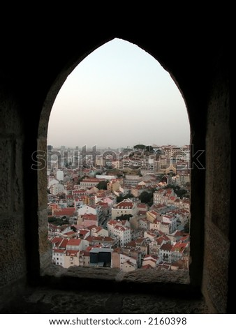 View to the tile roofs in the old Lisbon centre Alfama through the loop-hole. - stock photo