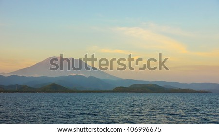 View to the volcano on the Bali island from the ocean, sunset, soft focus, soft light, background