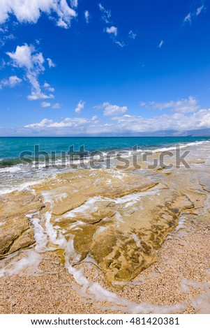 View to tide wave over pebbles and rocks on the beach near Acharawi village, Corfu, Greece.