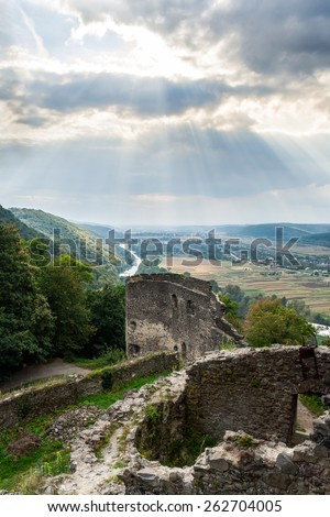 view to village in vally from stone wall of an old ruined castle in the mountains - stock photo