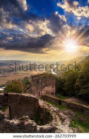 view to village in vally from stone wall of an old ruined castle in the mountains in sunset light - stock photo