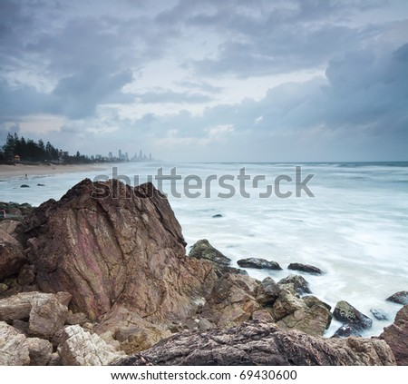 view towards the city from the beach with rocks in foreground
