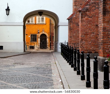 View towards the old town of Warsaw in Poland showing the multi colored houses through an archway - stock photo