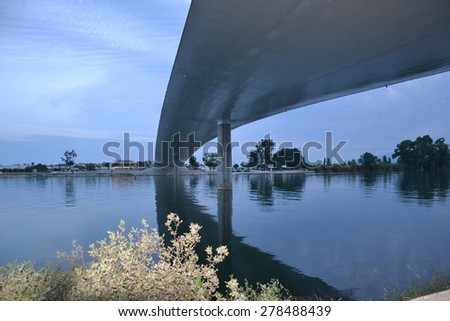 View under a bridge across the river at night - stock photo