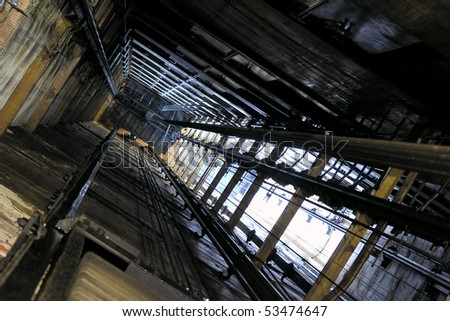 View up an old freight elevator shaft. - stock photo