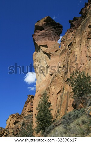 view up at monkey face rock spire in Smith Rock State Park - stock photo