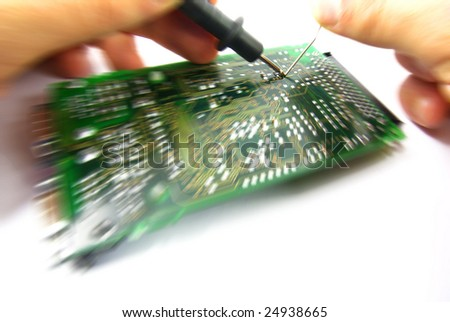 View with motion effect of a circuit board being repaired. - stock photo