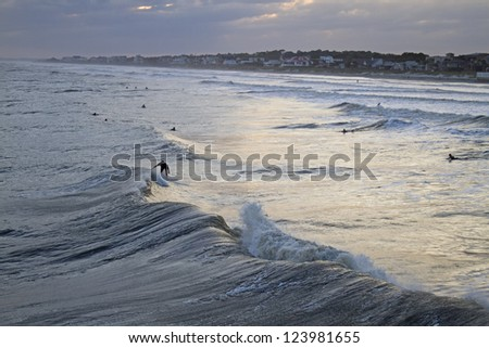 Viewed from offshore, surfers at Folly Beach, South Carolina, surf waves from Hurricane Sandy near sunset on October 25, 2012 - stock photo