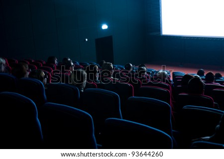 viewers watch a 3D motion picture in special glasses - stock photo