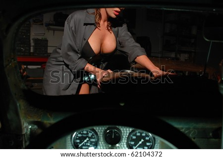 Viewing a Pin Up Girl through the Window of a Classic Car - stock photo