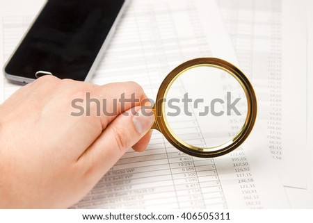 Viewing of the report on work in the table. Documents on analytics of finance. A magnifying glass in the man's hand. Desktop of the financier. - stock photo