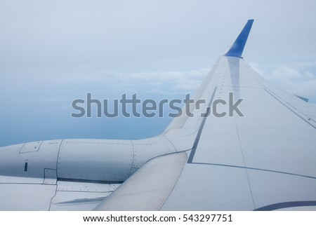 viewpoint Wing of windows airplane flying above the clouds in the sky