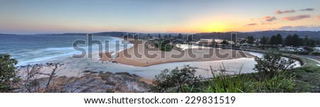 Views from North Narrabeen Head with Narrabeen lakes entrance and Narabbeen beach at sunset.  Panorama.  Note motion in leaves. - stock photo