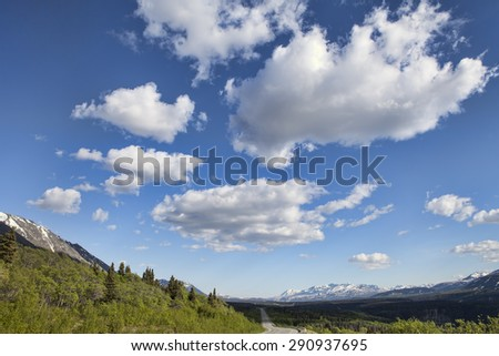 Views from the Haines Highway in Yukon Territory Canada in summer with puffy clouds. - stock photo