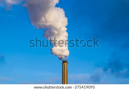 Views of clouds of white smoke from the chimney on background of blue sky - stock photo