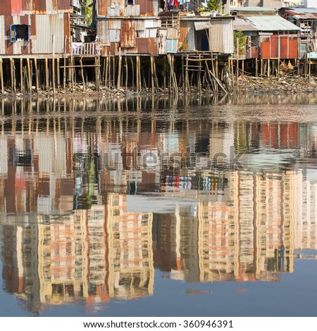 Views of the city's Slums from river. In water reflection of the new high-rise buildings. Ho Chi Minh City, Vietnam.