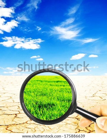 views of the desert with a magnifying glass on a background of green field with a blue sky - stock photo