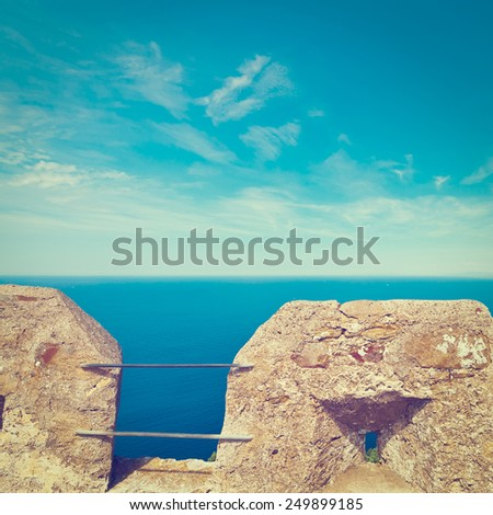 Views of the Mediterranean Sea through the Battlements of a Medieval Fortress in Italy, Instagram Effect - stock photo