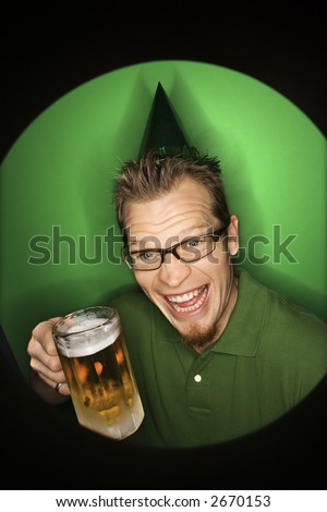 Vignette of adult Caucasian man on green background wearing green hat and holding beer. - stock photo