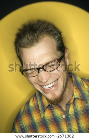 Vignette of adult Caucasian man on yellow background laughing. - stock photo