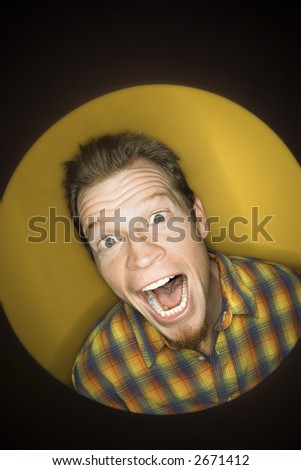 Vignette of adult Caucasian man on yellow background making funny face at viewer. - stock photo
