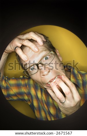 Vignette of adult Caucasian man on yellow background pulling at face and looking stressed out. - stock photo