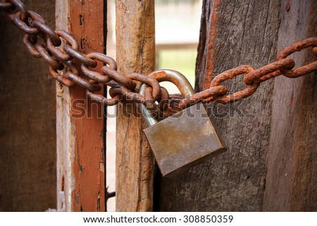 Vignette old key and rusty chain. Vignette lock key and chain. Old key and rusty chain on wood gate. Grunge key and chain on gate. Rusty key on gate. Rusty chain on wood gate. Dirty key and chain. Key - stock photo