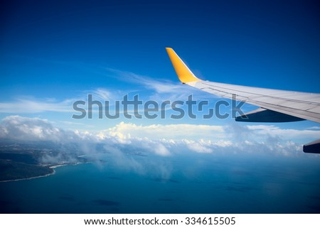 vignette picture, Wing of an airplane flying above the ocean. - stock photo